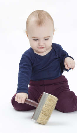 young child in blue shirt with brush on light background photo