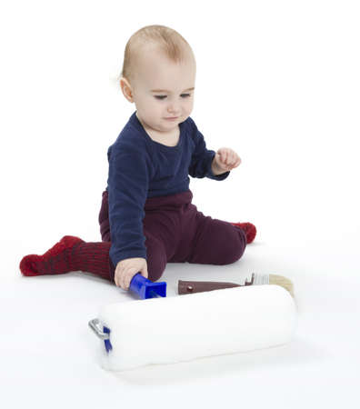 young child with painters equipment in light background photo