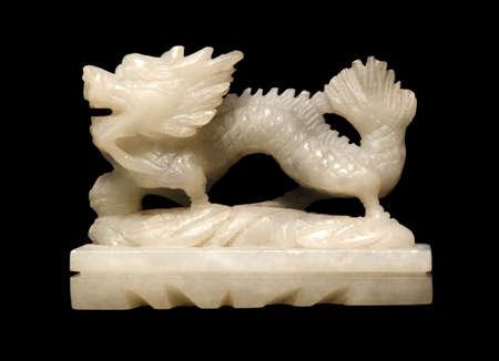 harridan: peque�a figura de piedra de jab�n blanco que muestra un drag�n chino en fondo negro Foto de archivo