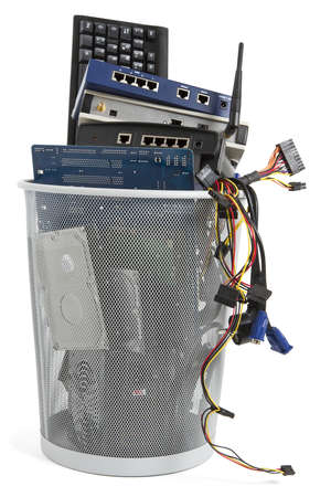 electronic scrap in trash can  keyboard, power supply, router, cables, logicboard, hard drive, switch Stock Photo