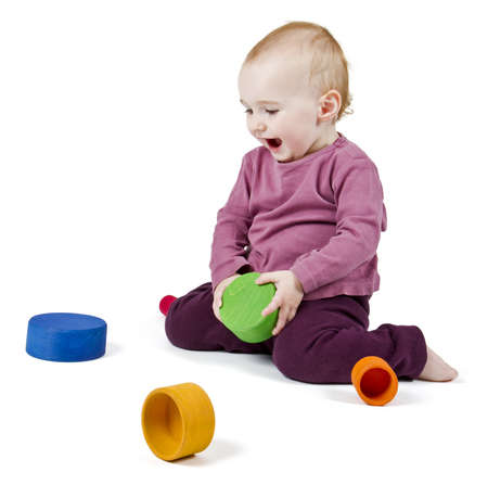 young child playing with colorful toy blocks in white background photo