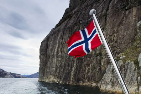 steep mountain over fjord with flag in foreground photo