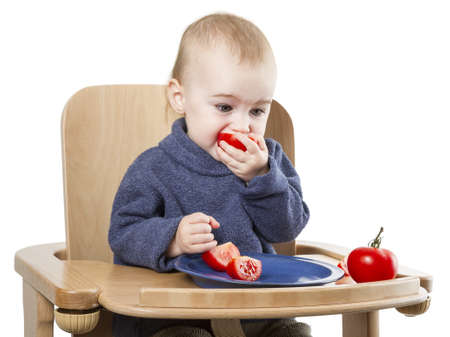 young child eating in high chair isolated in white backgound photo
