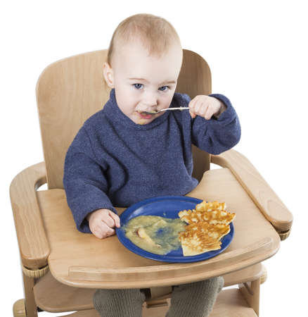 young child eating in high chair isolated in white backgound