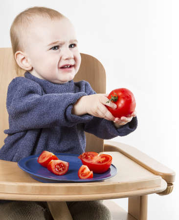 huffy: young child eating in high chair isolated in neutral background Stock Photo