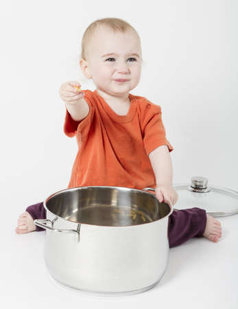 baby with big cooking pot on neutral background photo