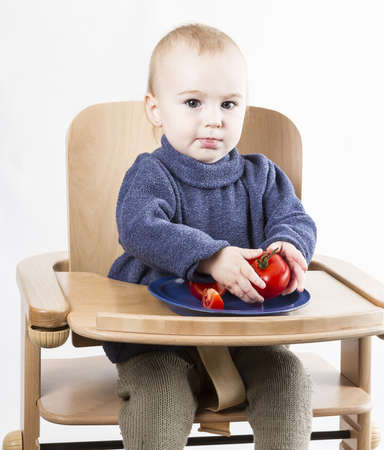 young child eating in high chair  neutral grey background Stock Photo