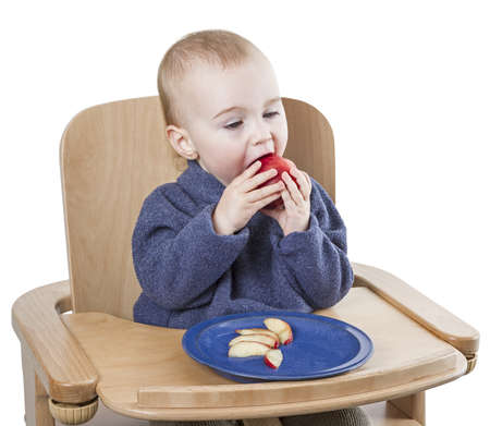 young child eating in high chair isolated in white background photo
