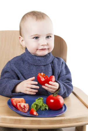 young child eating tomatoes in high chair isolated in white backgound photo