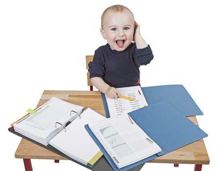 young child working at writing desk in light background photo