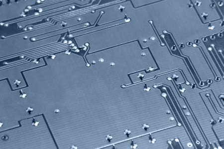 miniaturization: blue toned abstract detail of a circuit board backside