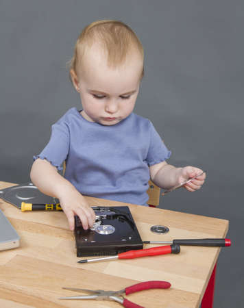 collet: child working at open hard drive in grey background with laptop computer