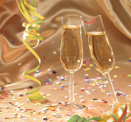 fluting: party background with filled champagne glasses in floating satin back with streamers and confetti Stock Photo