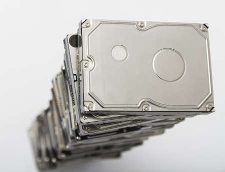 high stack of used hard drives in light background