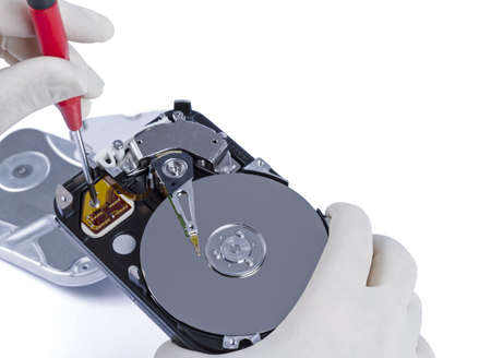 bulk memory: technician with open hard-disk and screwdriver in light background