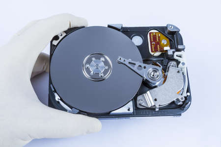 fixed disk: technician with open hard-disk in light background