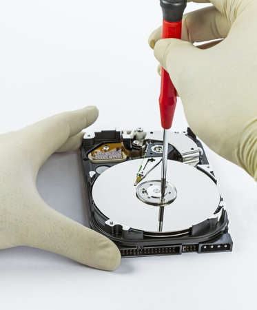 technician with open hard-disk and screwdriver in light background Stock Photo - 16063836