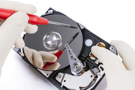 fixed disk: technician with open hard-disk and screwdriver in light background