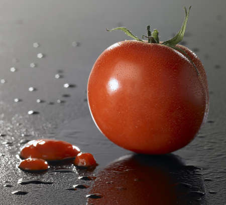 precipitate: studio shot of a tomato and ketchup on wet surface