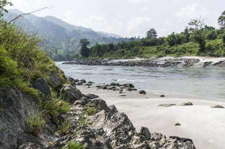 runnel: river in sun koshi, nepal with forest and small buildings