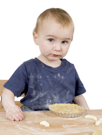 cooky: young child making cookies on small wooden desk