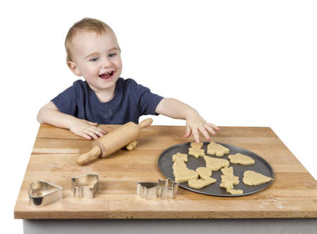 12 18 months: young child making cookies on small wooden desk