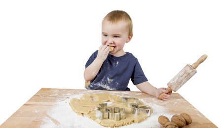 young child making cookies on small wooden desk