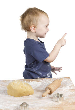 bickie: young child making cookies pointing at side