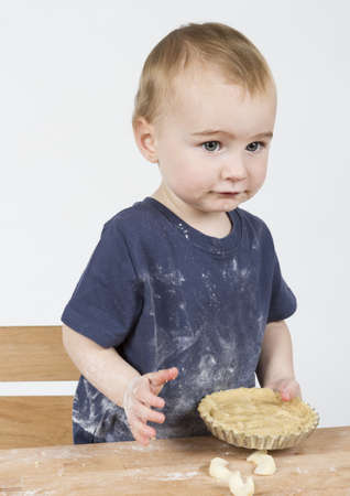 young child making cookies on small wooden desk photo