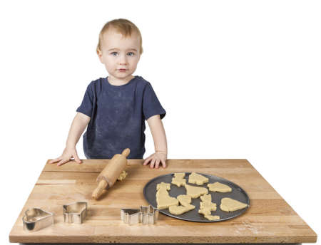 bickie: young child making cookies on small wooden desk