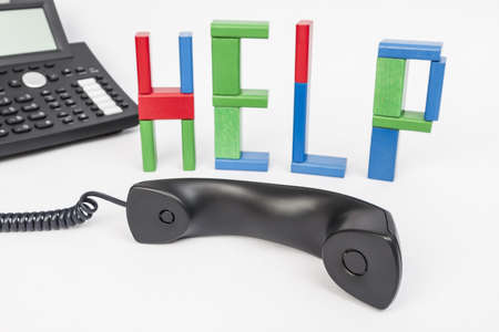 the word help made with toy bricks and a phone in background  telephone receiver in the foreground