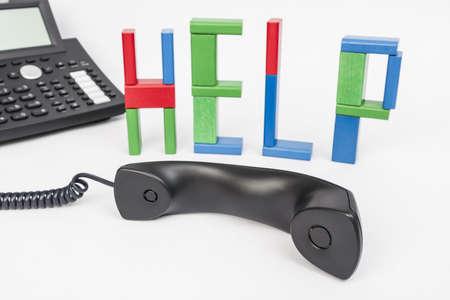 das Wort Hilfe mit Spielsteinen und ein Telefon im Hintergrund Telefonhörer in den Vordergrund gestellt