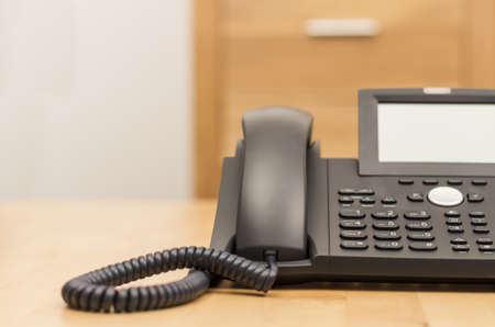 voip: modern black phone on wooden desk with blurred background Stock Photo