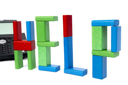 the word help made with toy bricks and a phone in background  isolated on white background Stock Photo - 17457329