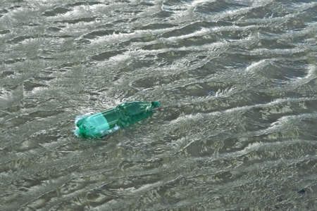 wavily: pollution theme with a green plastic bottle floating on water surface Stock Photo