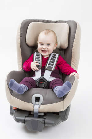 laughing child in booster seat for a car in light background