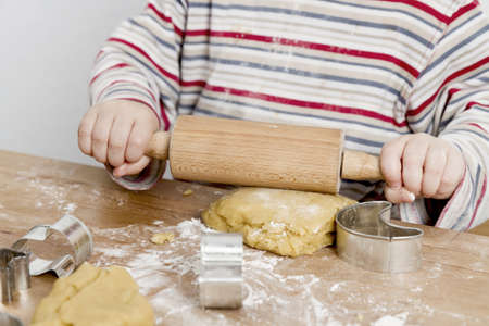 bickie: image of hands and desk  child is making cookies with a rolling pin