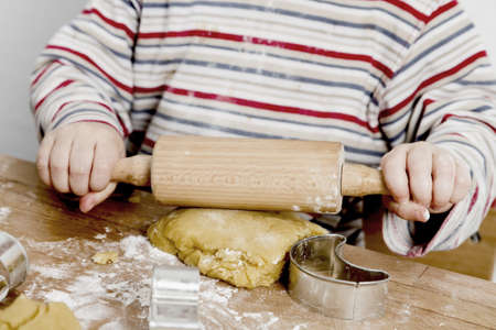 bickie: image of hands and desk. child is making cookies with a rolling pin Stock Photo