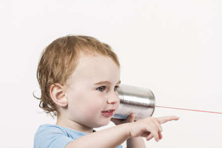 young, happy child listening to tin can phone and pointing at speaker caucasian child in horizontal image