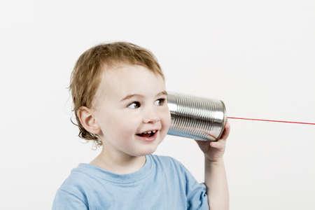 glückliches Kind in hellgrauem Hintergrund hört Blechdose Telefon. horizontale Bild