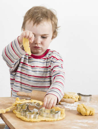 young child working with dough on wooden desk with flour. Vertical image photo