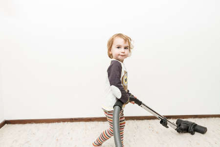 household chore: cute child doing household chore with vacuum cleaner Stock Photo