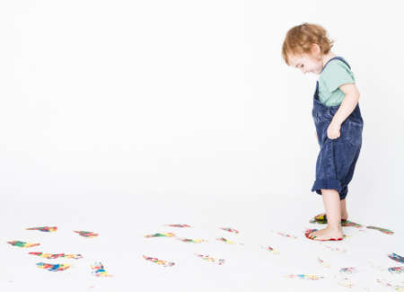 girl making colored footprints on the floor  studio shot with light grey background Stock Photo