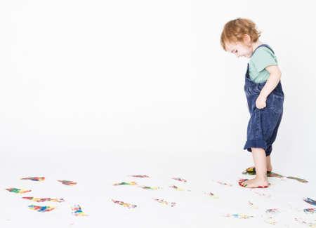 Mädchen, das farbige Fußabdrücke auf dem Boden Studio gedreht mit hellgrauem Hintergrund Lizenzfreie Bilder