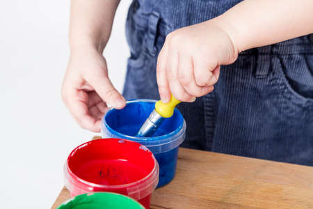 child holding brush in blue paint tub photo