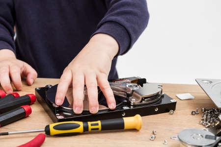 Open Festplatte auf dem Schreibtisch mit Werkzeugen und Hand des Kindes studio shot