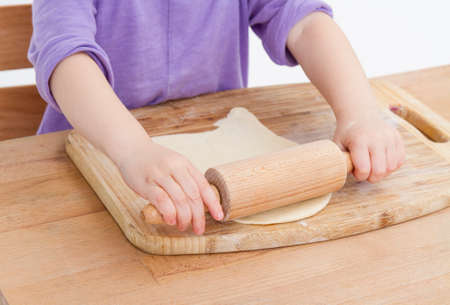 child making fresh pizza beginning with rolling out the dough photo
