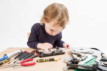 young child repairing open hard disk drive with different tools Stock Photo