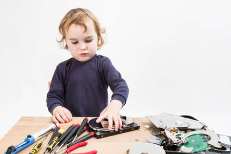 child repairing computer part  studio shot in light grey background photo