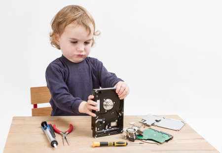 fixed disk: young child repairing open hard disk drive with different tools Stock Photo